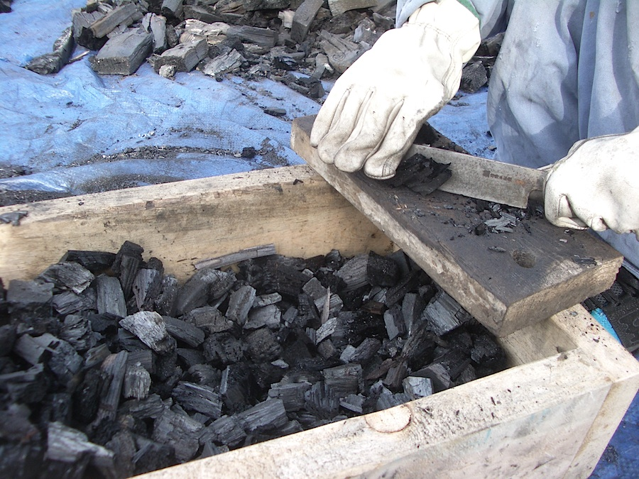 Chopping and sorting blacksmithing charcoal by hand.